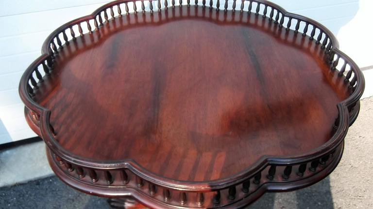 Mahogany table with scalloped gallery edge top. A center carved column resting on three carved paw foot legs. Solid mahogany with a nice reddish brown finish.