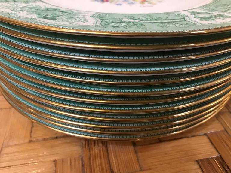 Rare set of 12 custom order service plates by Wedgwood with the artist signature L. Adams. The apple green toile borders with hand-painted Dresden floral centres. Each one slightly different and all signed by the artist. The mark on the back dates