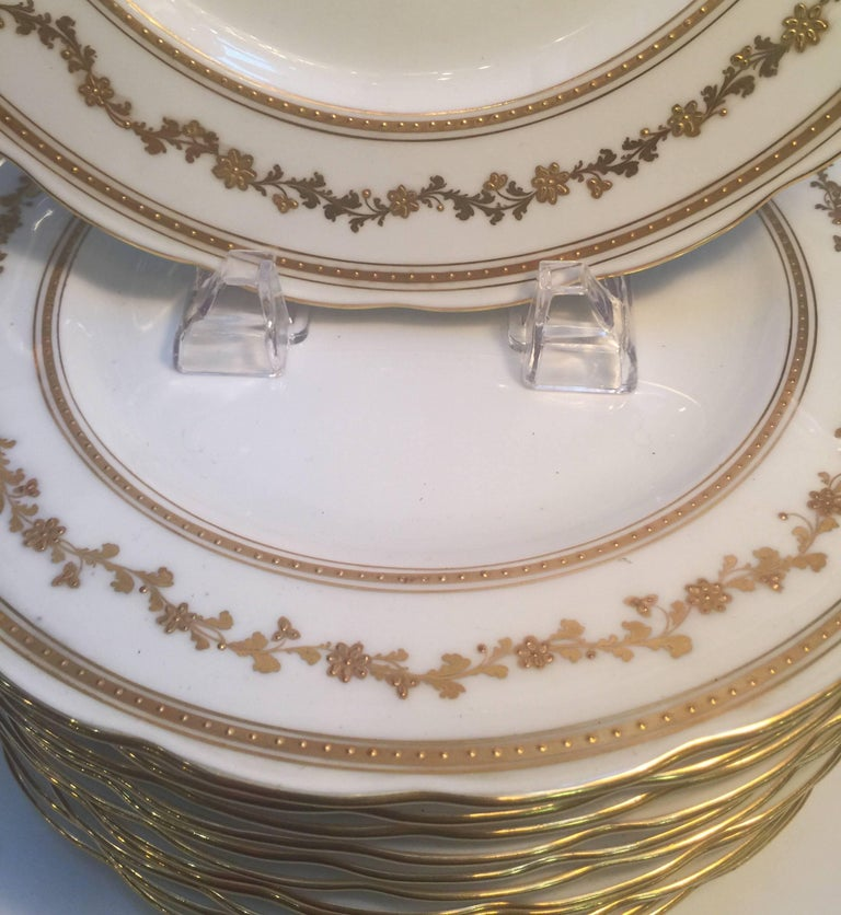 Elegant set of 12 raised gilt border dinner service plates with layered gold bands and floral band. The bone white background with scalloped edge.