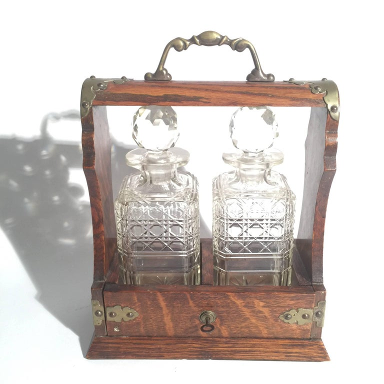 Late 19th century English oak Tantalus with two decanters. The oak caddy with brass mounts with top handle. Retains key.