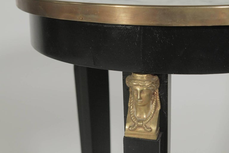 Pair of Hollywood Regency ebonized mirror top side tables with bronze gilt mounts. The Empire style with updated black finish and mirrored tops. The round tops with intentionally distressed mirrors supported by ebonized bases with ormolu mounts.