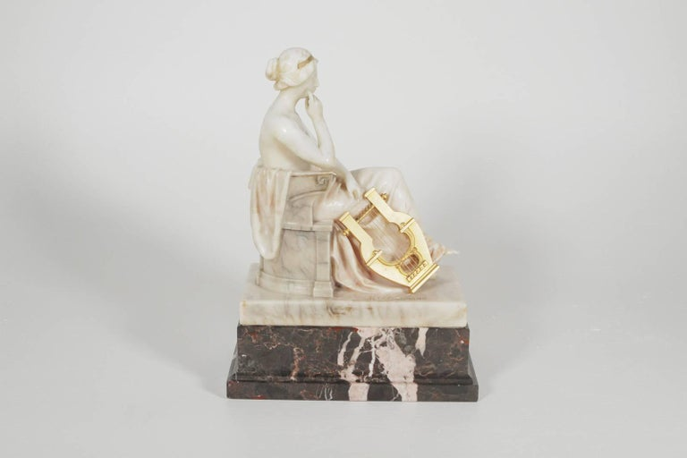 German marble and ormolu sculpture of a seated muse with harp signed Hintzelman-WithGladenbeck-Berlin Seal Germany, circa 1910-1925 The gorgeous carved sculpture in Carrara marble resting on a black marble base with a gilt bronze harp. Measures: