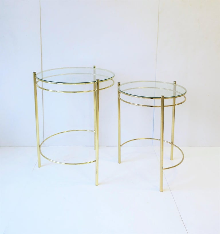 A set of round metal brass plated and glass top nesting end tables or side tables. Set can work as an end table/side table combo.   Tables measure: Top: 22.5 in. height x 17.25 in. diameter Nesting: 19.75 in. height x 15 in. diameter.