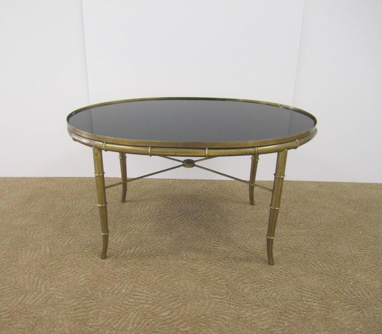 A very beautiful Mid-20th Century Italian oval gold cocktail or coffee table with a brass 'bamboo' detailed frame, X stretcher design at base, and inset custom black mirrored glass top, Italy, circa 1960s.   Table measures: 29
