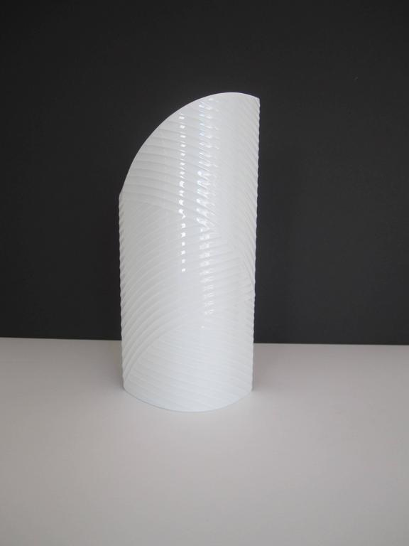 A beautiful white porcelain ceramic pottery vase from Germany. Vase has an asymmetric design and textured details around. Vase measures 11