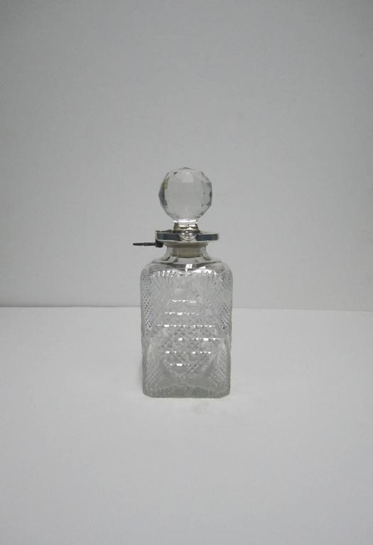 Beautiful and substantial antique English crystal and sterling silver spirit/liquor decanter with lock and key, circa early 20th Century, England. Decanter has a multifaceted round cut crystal stopper with mounted sterling silver stopper, neck, and