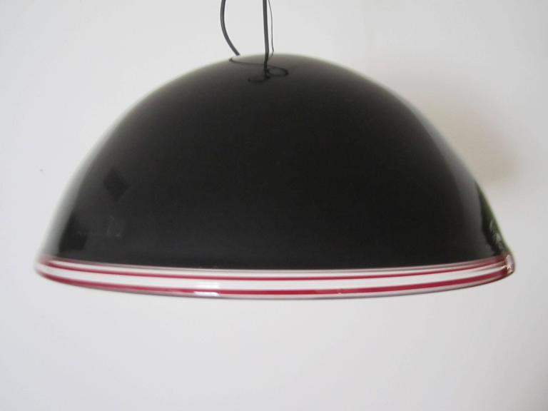 A beautiful and substantial Modern style or Post-Modern [Postmodern] period black Italian Murano art glass dome chandelier pendant hanging light. Murano glass is predominantly black with clear and red/burgundy/ox blood art glass trim. With marker's