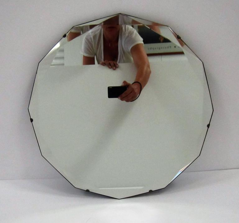 A beautiful vintage Hollywood Regency style 12 sided (dodecgon) beveled edge wall mirror. Beautiful intersecting bevel at each point (12) around mirror edge.   Mirror is 17 in. in diameter.   Item available here online. By request, item can be made