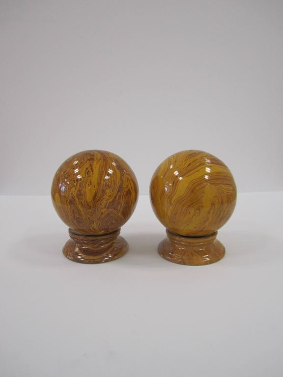 A pair of Italian round ceramic marbleized glazed decorative spheres on pedestal bases. Well made with a beautiful marble pattern, covered with a light glaze. Colors include swirls of deep yellow/mustard and dark red/burgundy hues.  Measurements: 6