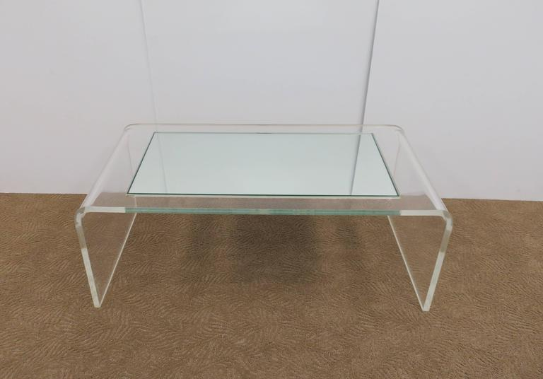 A Modern Lucite and glass mirror 'waterfall' coffee table in the style of designer Charles Hollis Jones, circa 1970s. Custom mirrored glass top is 3/8 in. thick. Lucite base is 1 in. thick. Mirrored top sits 'inset' into Lucite base; easily