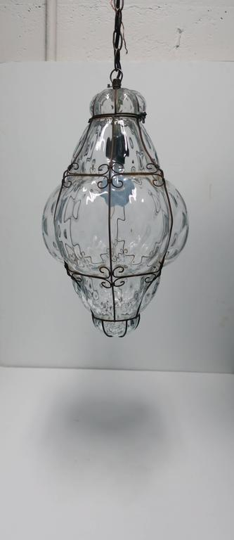 A gorgeous, relatively large, clear Italian one lamp/bulb lantern pendant hand-blown glass light embraced by decorative metal, Italy, circa 1950s.  Measurements include: 19.5