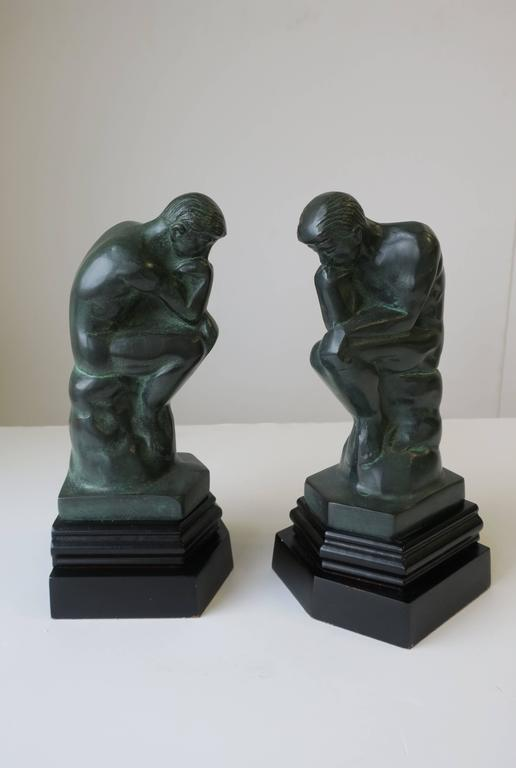 A great pair of vintage 'Thinker' male sculpture bookends in dark green with black bases, each measuring 9.25 in H.