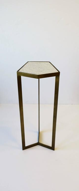 A minimalist geometric matte gold tone metal side or drinks table with white granite marble stone top. A small and convenient drinks table.   Table measures: 21 in. H x 7 in. x 7 in.