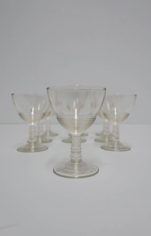 Set of nine beautiful Modern clear glassware set. Ribbed detailing and ball stem. Great for Champagne or other wine or spirit, circa 1920s.   Each measure 4 in. H x 2.75 in. diameter.