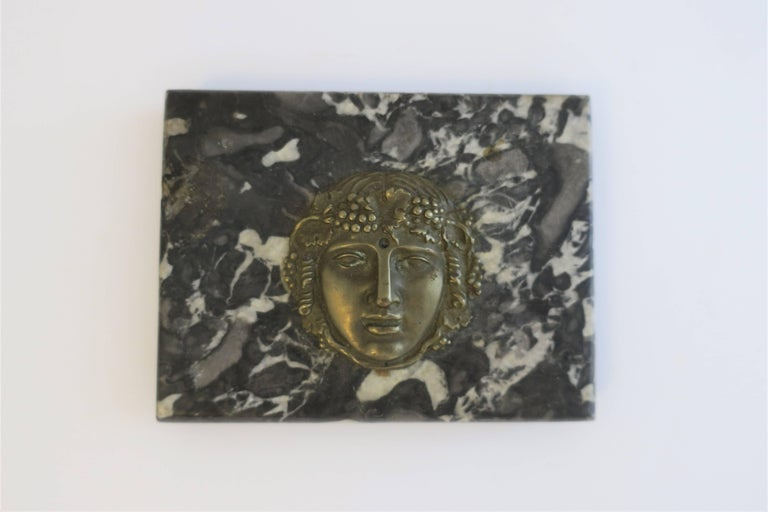 A substantial Italian black and white marble with brass face sculpture decorative object, paperweight, or deck accessory, in the Classical Roman style, circa early to mid-20th century, Italy.   Piece measures: 4.63 in. W x 3.50 in. D x 1 in. H  Item