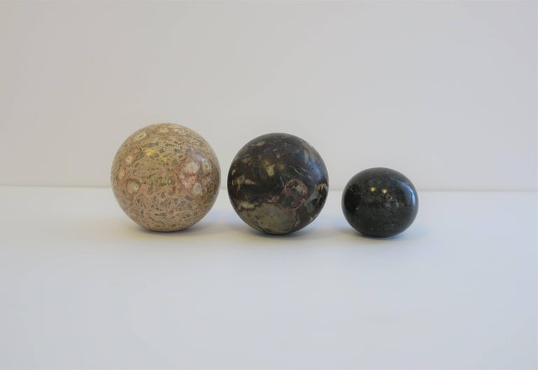 A set of three modern marble stone decorative spheres, circa 1970s. Black sphere has a 'flat' bottom   Amongst the three sphere's, colors include: cream, sand, very light pink or flesh color, blue, green, black, dark red and traces of