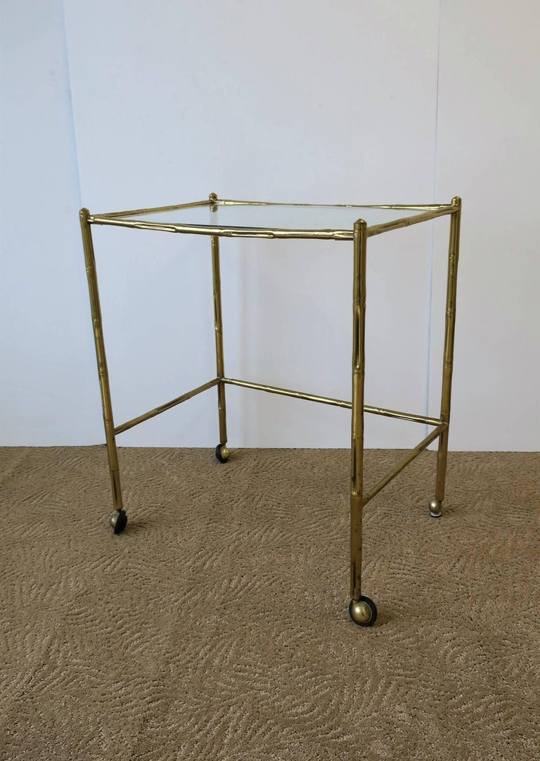 A great early Mid-20th century Italian brass and glass bar cart or tray-table style table, mid-20th century, Italy, circa 1940s. Brass frame has a 'bamboo' design with an inset glass top.   Piece measures: 20.75 in. W x 13.75 in. D x 24 in.
