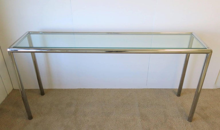 A substantial vintage modern chrome and glass console table, circa late 20th Century. Frame is tubular in shape with a substantial inset tempered glass top. Console's depth is 15 inches.   Measurements: 15 in. D x 59 in. W x 29 in. H.  Item