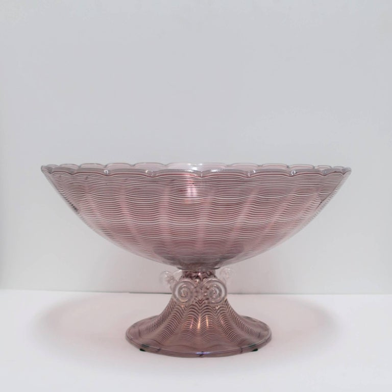 A very beautiful and relatively large vintage Italian Murano art glass urn form centerpiece bowl. Piece has a scalloped edge around top and clear applied art glass swirls on base. Centerpiece hues are deep purple or plum and clear translucent art