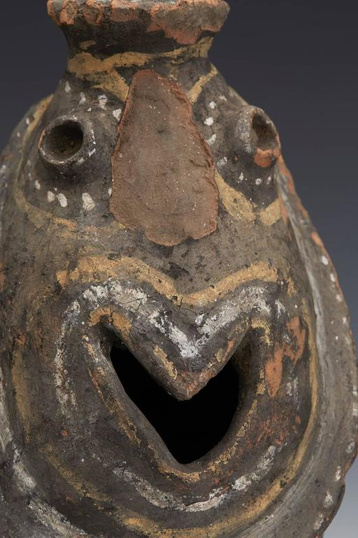 We offer this interesting Kwoma tribe ceremonial pottery head jar of grotesque form and originating from Papau New Guinea and believed to date from the 19th or early 20th century. The earthenware jar is of elongated rounded shape and modeled as a