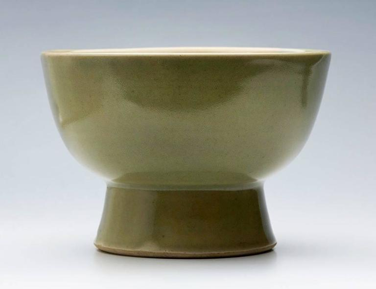 A Leach Pottery studio pottery footed bowl decorated in celadon glazes by David Leach and dating from the early to mid-20th century. The rounded porcelain bowl stands raised on a conical shaped foot and is decorated in celadon green glazes with a