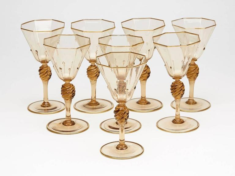 A very fine set eight Murano MVM Cappellin amber wine glasses with octagonal bowl with applied tear drops to a wrythen knopped stem and spreading circular foot and with gilded edging. The glasses are not marked.  MVM Cappellin & C. was founded by