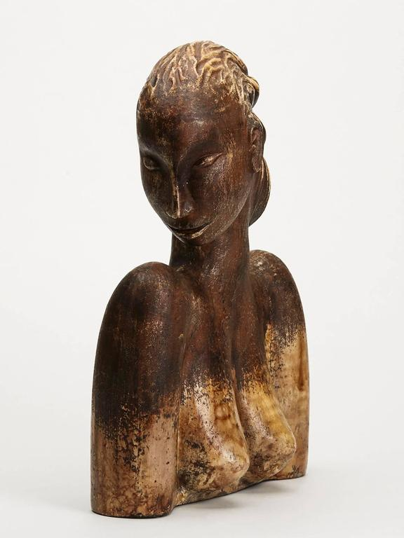 A stylish and large Continental terracotta profile bust of a lady looking sideways, the hollow and finely potted figure decorated in brown glazes. The sculptural figure is not marked.