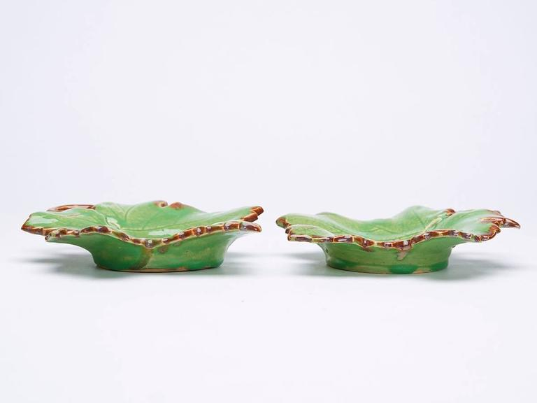 A pair of French Greber art pottery dishes modeled as leaves, the stems forming handles decorated in green and brown glazes with Fine surface veining. Made in Beauvais and probably by Charles Greber (1853-1935) the stoneware dishes Stand on a