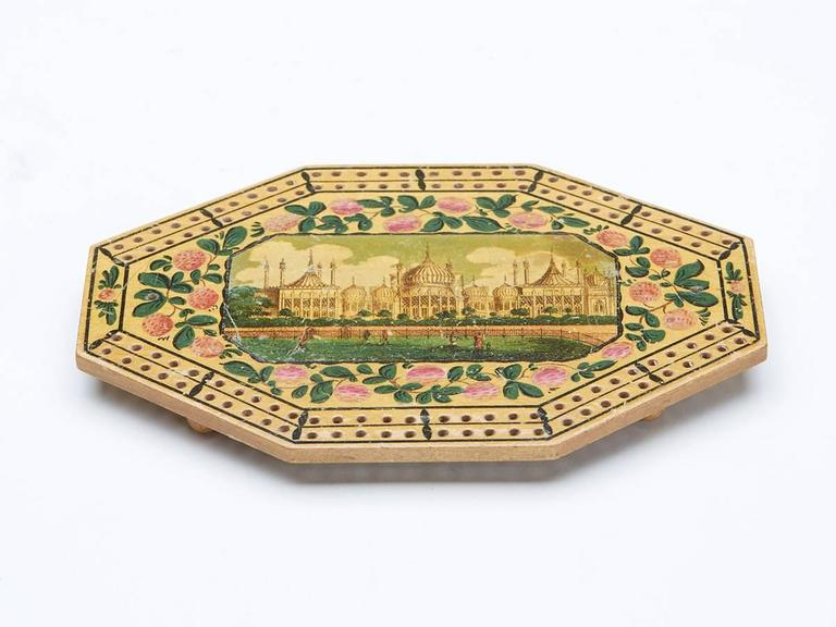 A very rare Georgian octagonal wooden cribbage board with a central framed scene of Brighton Pavillion within a floral border with peg holes arranged around the outer edge within simple painted line borders. The cribbage board stands raised on four