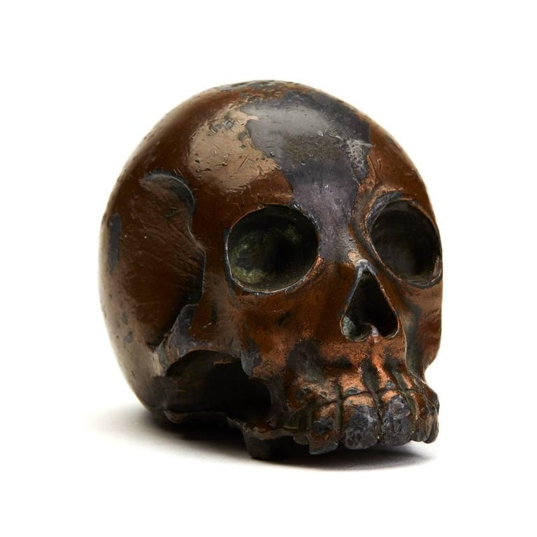 An antique Japanese Meiji lacquered antimony Okimono modelled as a naturalistic human skull with a lacquered brown finish and traces of gilding to the base. The heavily made skull is well proportioned and has a raised seal signature mark to the
