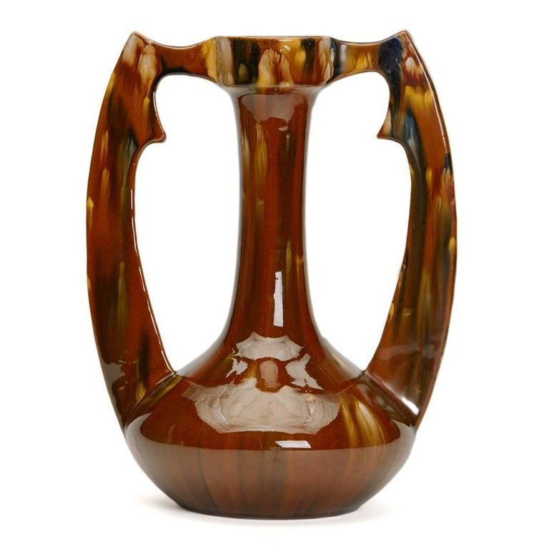 A stunning Art Nouveau French twin handled earthenware vase by Clement Massier decorated with brown, yellowand blue streaked glazes. The vase has an impressed CLEMENT MASSIER GOLFE JUAN.