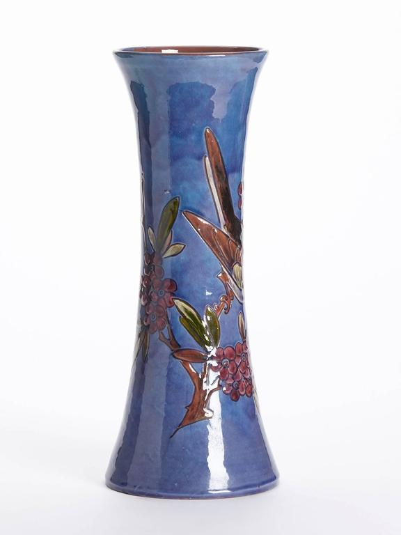 An unusual art pottery vase of trumpet shape decorated with a bird perched on a fruiting branch by William Baron. The tall waisted vase is incised and hand decorated and incised with a garden bird perched on a branch with berries painted in colours