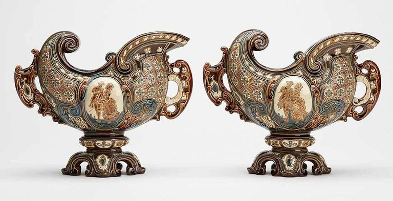 A stylish pair of antique Bohemian Majolica console bowls or vases elaborately decorated by Gerbing & Stephan. The earthenware bowls Stand raised on a narrow pedestal foot with helmet shaped bodies with central panels with incised courting figures