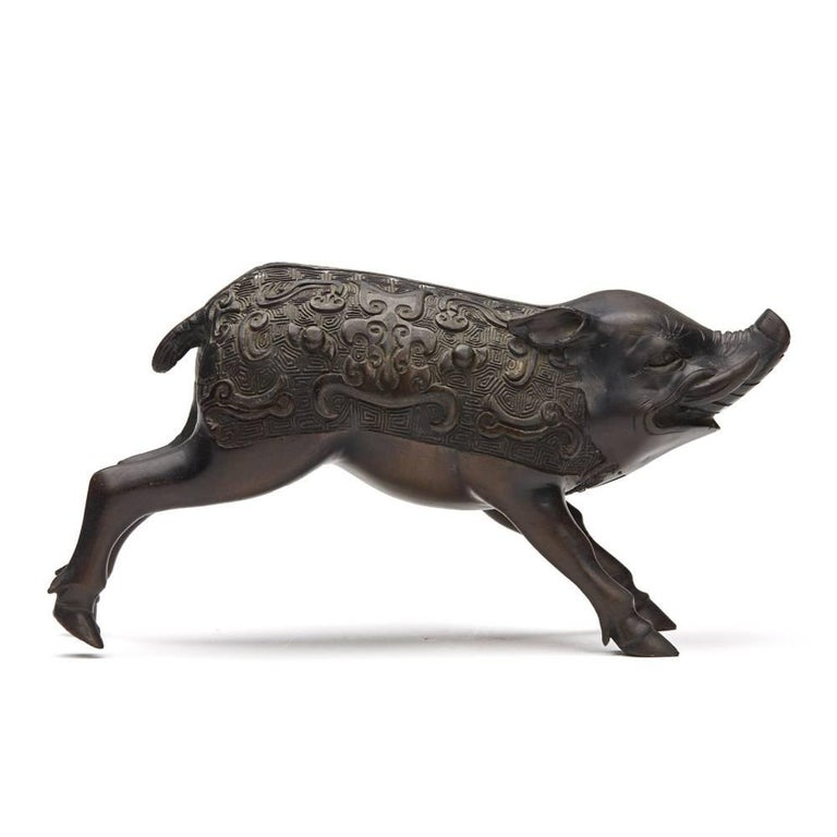 A fine and unusual antique Japanese Meiji bronze figure of a wild boar, the body with a detailed patterned relief moulded design. The running male boar has good facial features with extended canine teeth and is not marked.