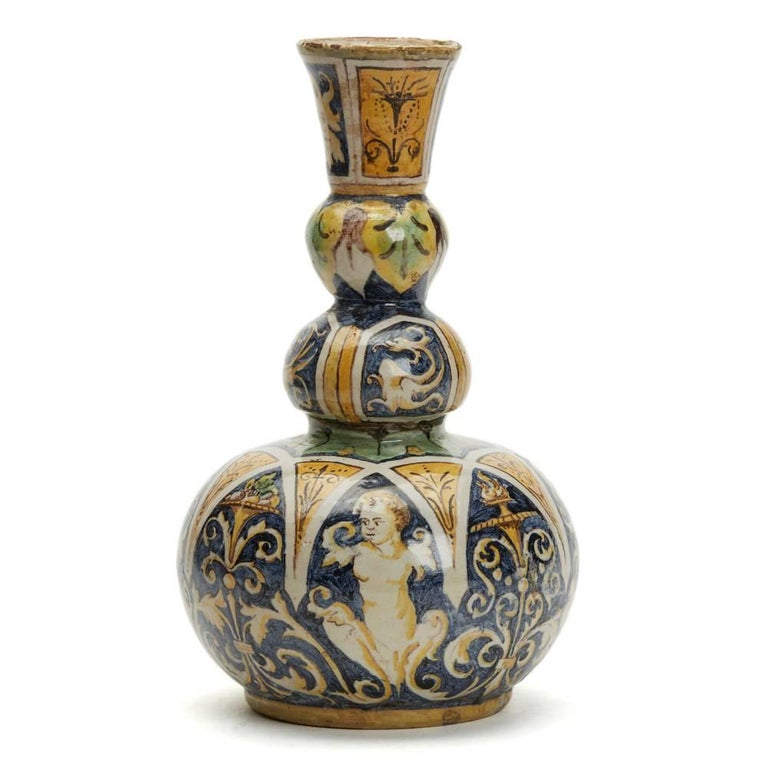 A stunning and rare antique Italian Maiolica pottery triple gourd vase hand-painted with classical stylised figurative and scroll designs in typical Maiolica yellow, blue, green, brown and white colors. The earthenware vase a squat rounded bulbous