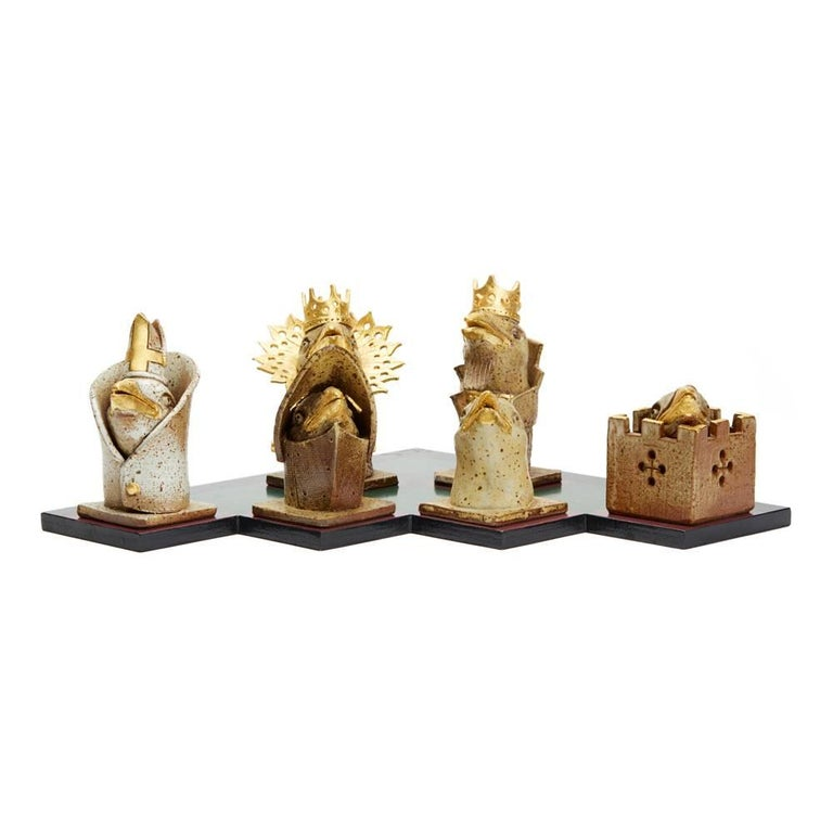 An unusual and stylish Kenneth Breeze Studio Pottery chess pieces and board sculptural installation comprising of six chess pieces and a hand-painted cut-out board. The chess pieces include a king, a queen, a bishop, a knight. A rook and a pawn each