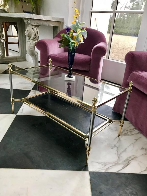 This stunning Pompeian style coffee table is made of solid elements throughout. Maison Jansen at it's finest!  The original top is crystal glass, the shelf below has the original black leather and is tooled with a Meander Pattern on the