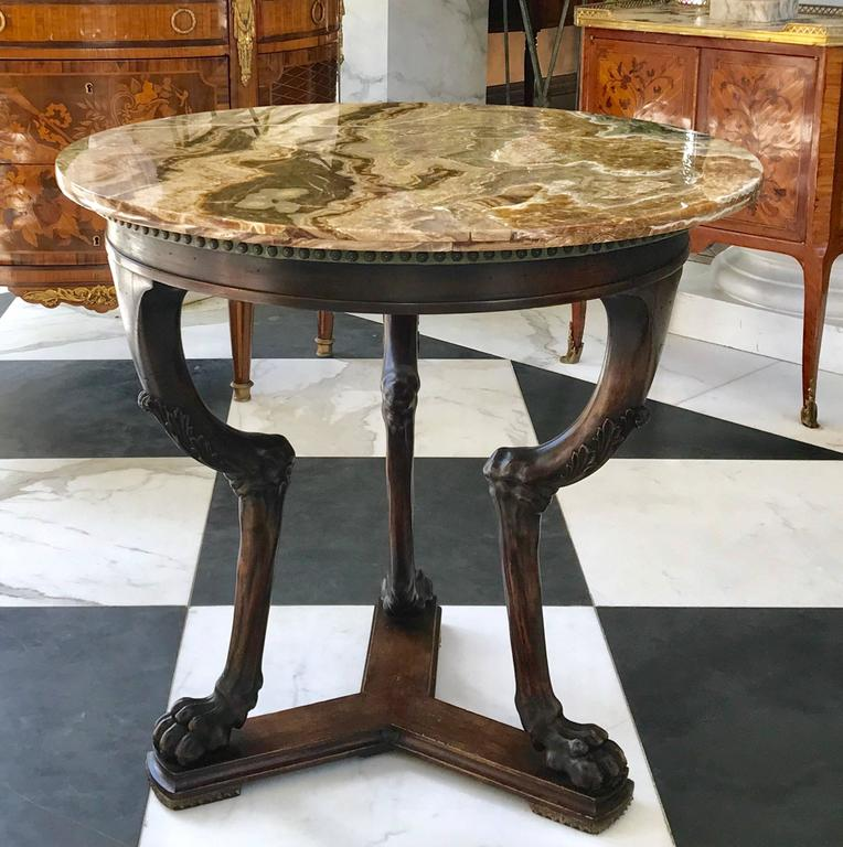 This extraordinary neoclassical side table is hand carved in the mid 19th century in Italy. Made of walnut with a rare deep amber onyx top that will catch the eye of anyone. The elegance of this table is outstanding!  Made in Italy ca 1840