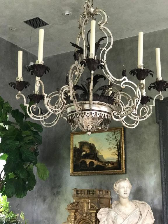This beautiful wrought iron & tôle nine-arm chandelier was created in the 1940s and inspired by a Louis XV French Chandelier form. The aged silver patina gives this Chandelier it's extraordinary look.