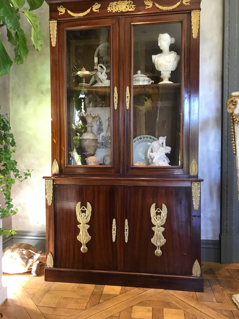 This beautiful pair of mahogany Empire bookcases is decorated with gilt bronze mounts portraying armorial motifs, winged Nike figures, swans and garlands. The glass doors are original.