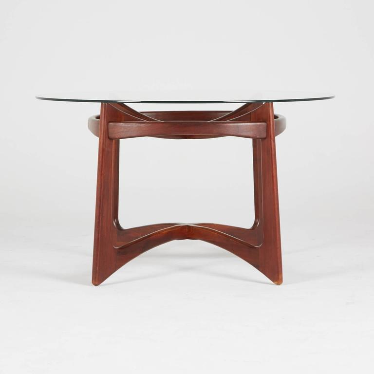 Designed by Adrian Pearsall for Craft Associates, circa 1960, a round glass surface rests on the sumptuous walnut base. This superb Compass dining table has the atomic, biomorphic qualities of Classic Mid-Century Modern design, though it coordinates