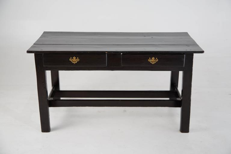 Sleek and simplistic black lacquered vintage wooden desk with brass ornate handle pulls. This desk features two pull-out drawers at the front and stretchers running along each side.