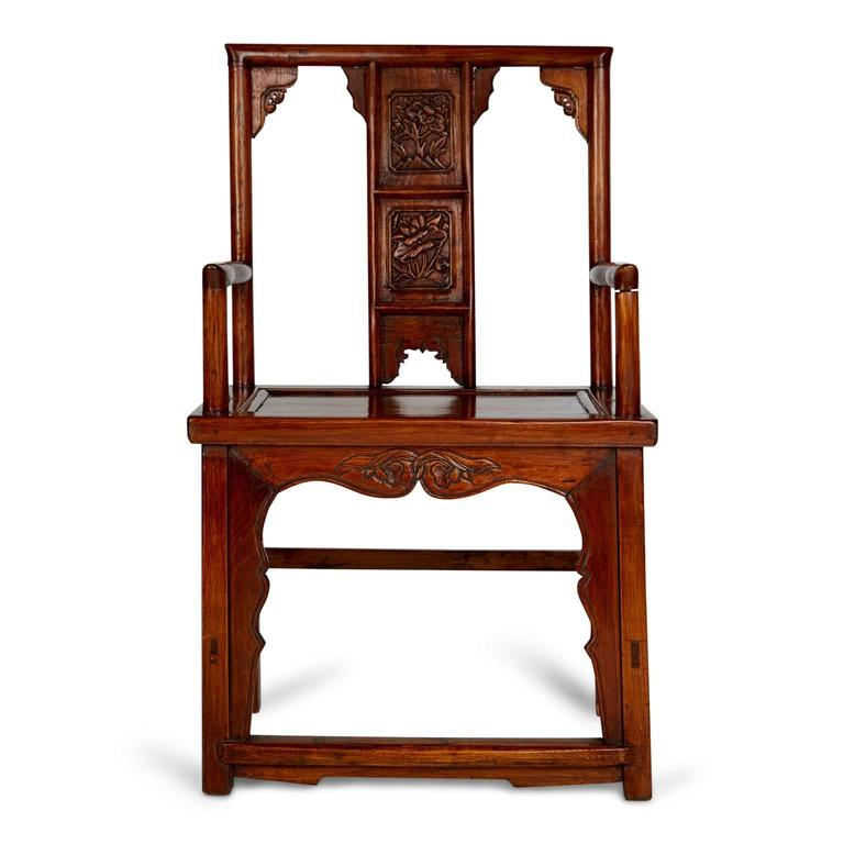 Pair of beautifully carved Chinese armchairs. These noble looking throne style chairs have been expertly crafted, central splats which feature floral carvings that mirror one another. There are also etched embellishments of the seat back and rail.