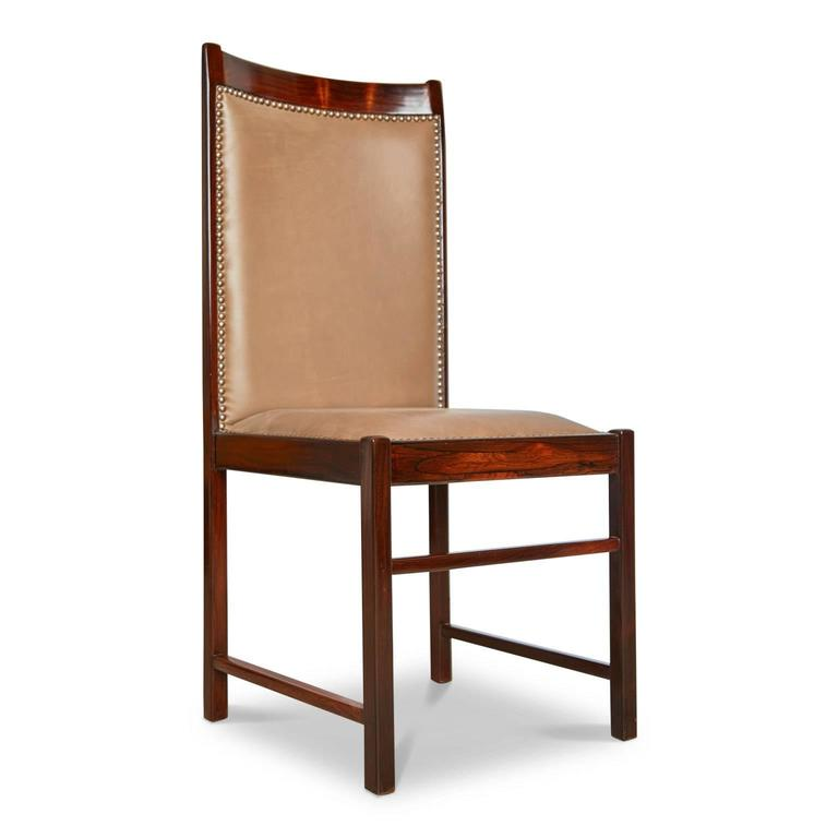 Single high back chair by Celina Moveis fabricated from solid rosewood and upholstered in a quality supple tan leather finished with bronze nailhead details. It should be noted that these chairs are handmade and therefore there may be a slight