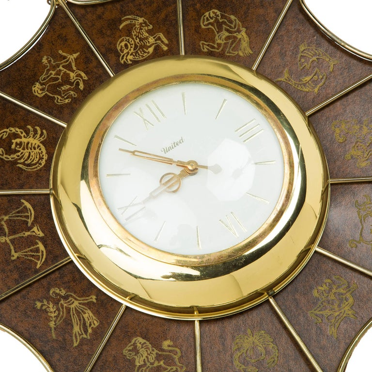 Wonderful starburst clock by United. Featuring twelve wood spindles, faux leather surface finish with embossed symbols of the zodiac, wire frame with white and brass face and Roman numerals. Would pair wonderfully in a chinoiserie styled room, a