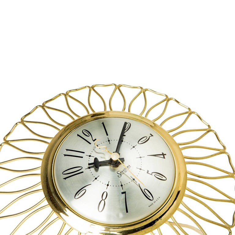 Wonderful Mid-Century Modern starburst clock by Sessions. Featuring circular wire detail with an aluminum brass face, Roman numerals and the letter 'S' on the minute hand. Plug at the back.