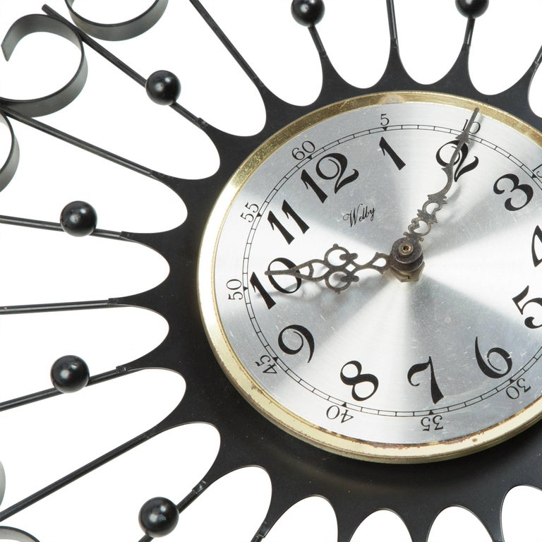 Wonderful sunburst clock by Welby. Featuring a sculptural iron work design with an aluminum face and black numbers. Plugs in at the back.   The archetypal design makes this clock appropriate for a number of locations, from Classic and contemporary