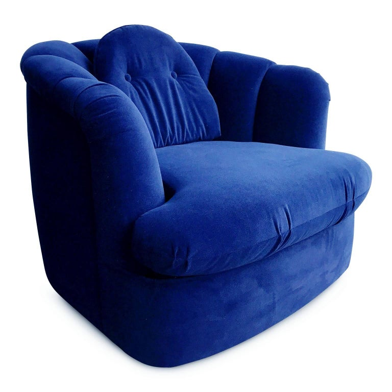 Elegant Milo Baughman swivel lounge chair for Thayer Coggin. This sumptuous armchair has been newly reupholstered in a rich navy velvet with channel tufting along the back and features an upholstered swivel base for ease of direction of