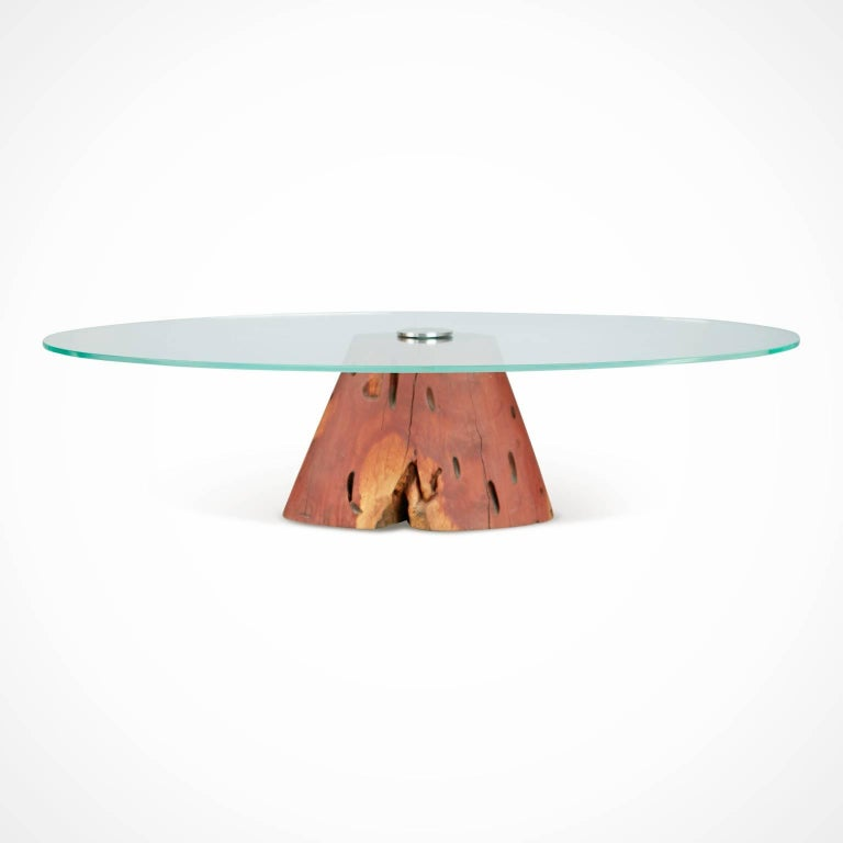 Custom live edge made coffee table by Brazilian designer Tunico T featuring a salvaged chunk of Jatoba wood which has been crafted to make a sturdy plinth base for a thick piece of oval shaped glass to be mounted. The glass is anchored by sturdy