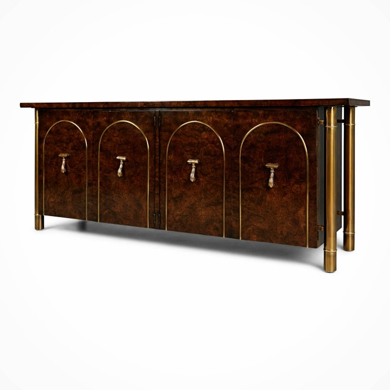 This Asian inspired credenza by William Doezema for Mastercraft features a burl wood finish with brass cylindrical legs running the length of the cabinet from under the top down to the floor. There are two sets of double doors with centrally placed